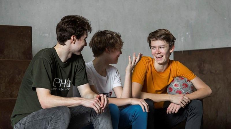 Tre unge drenge snakker og griner